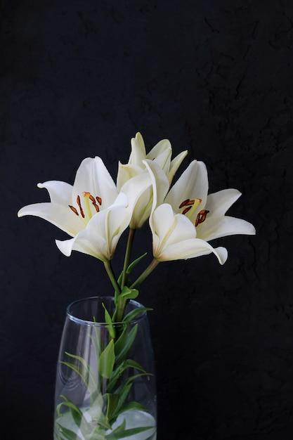 Bouquet de fleurs de lys blanc sur fond noir. Photo Premium