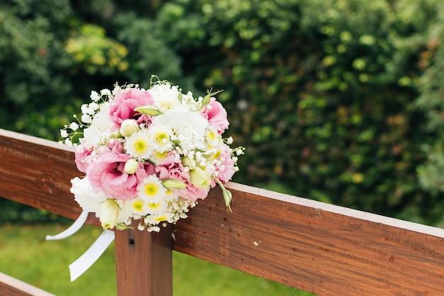 Bouquet de fleurs de mariage attaché sur une balustrade en bois dans le parc Photo gratuit