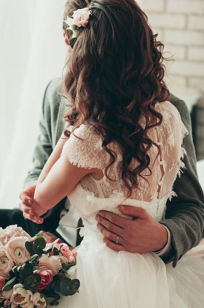 Bouquet De Fleurs De Mariage, Un Couple Assis Sur Le Lit, Vue Arrière Photo Premium