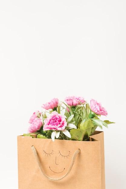 Bouquet de fleurs d'oeillets roses à l'intérieur d'un sac en papier brun Photo gratuit