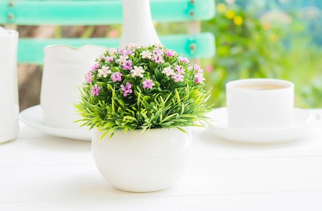 Un bouquet de fleurs en plastique dans un vase sphérique blanc au petit déjeuner. Photo Premium