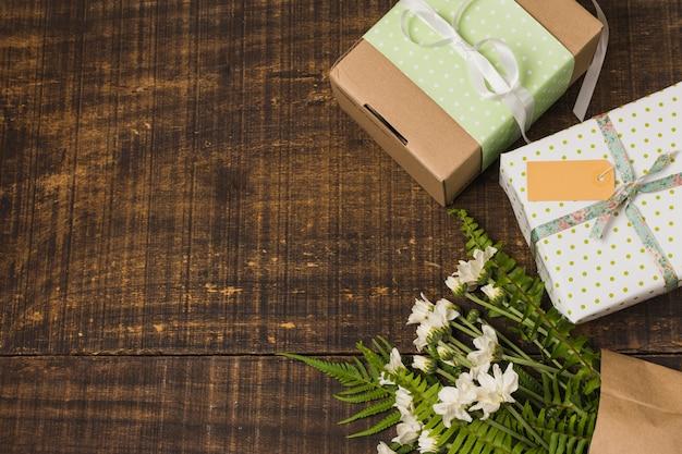 Bouquet de fleurs près de boîtes de cadeau emballés sur le vieux bureau Photo gratuit