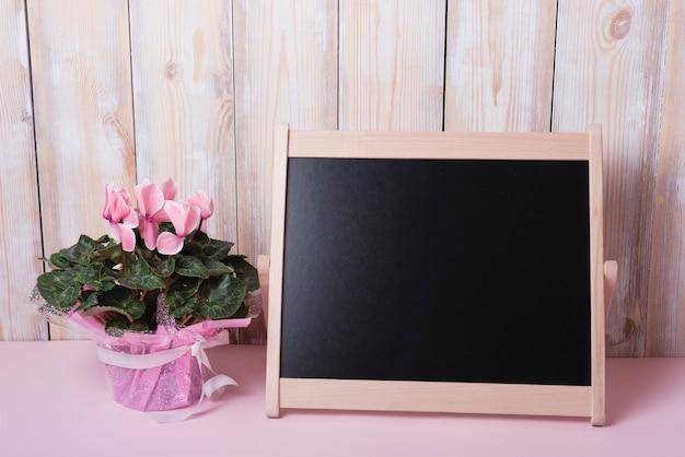 Bouquet de fleurs roses avec petit tableau blanc sur le bureau contre le mur en bois Photo gratuit