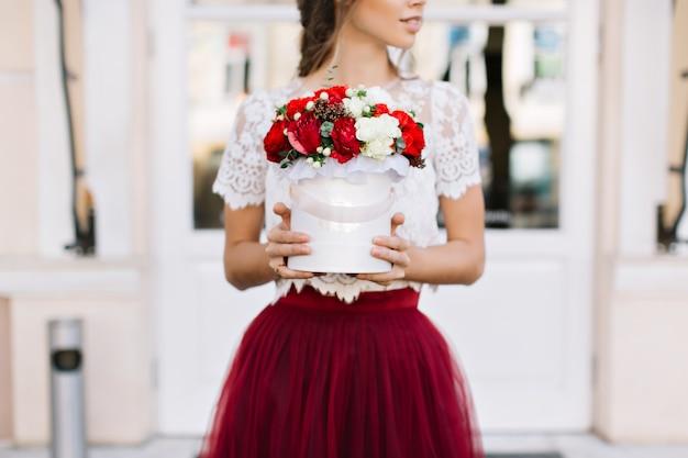 Bouquet De Fleurs Rouges Et Blanches Dans Les Mains De Jolie Fille En Jupe Marsala En Tulle Sur Rue Photo gratuit