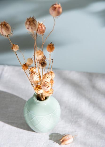 Bouquet De Fleurs Séchées Coquelicots Dans Un Vase Vert Sur Une Nappe En Lin Et Ombre Du Matin Sur Fond Vert Clair. Fermer Photo Premium
