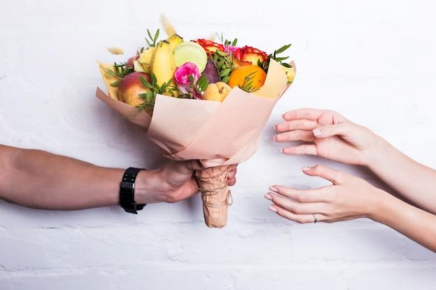 Un bouquet de fruits et de fleurs est donné par un homme Photo Premium