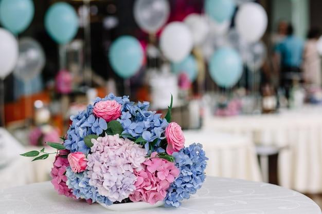 Le bouquet d'hortensias roses et bleues se trouve sur un tabl. blanc Photo gratuit