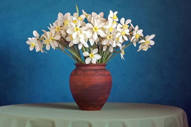 Bouquet de jonquilles dans un pichet d'argile sur un bleu. Photo Premium