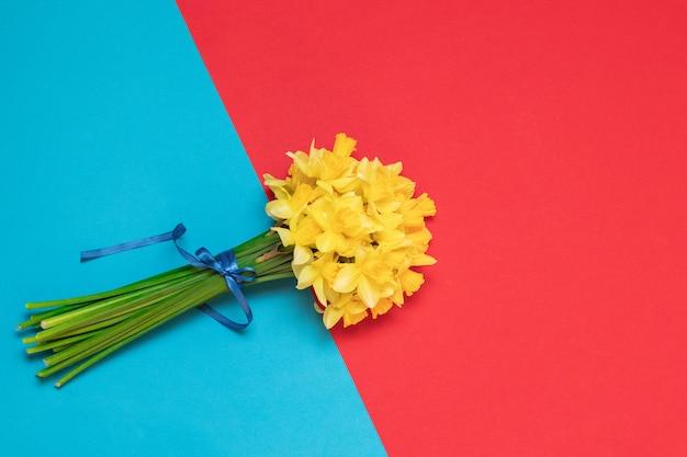 Bouquet de jonquilles jaunes fraîches dans des mains féminines sur fond avec un espace pour le texte Photo Premium