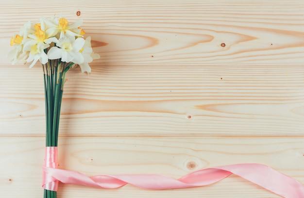 Bouquet de jonquilles avec ruban rose sur bois avec fond Photo Premium