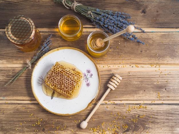 Bouquet de lavande; pot de miel; et pièce en nid d'abeille sur la plaque sur la table Photo gratuit