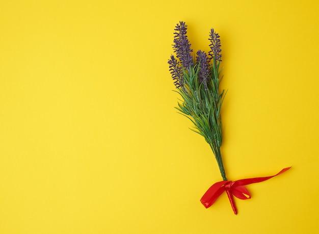 Bouquet De Lavande Et Ruban Rouge Sur Une Surface Jaune Photo Premium