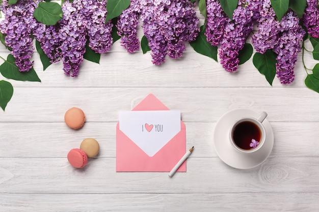 Un bouquet de lilas, une tasse de thé, une note d'amour et des macarons sur une table en bois blanche Photo Premium