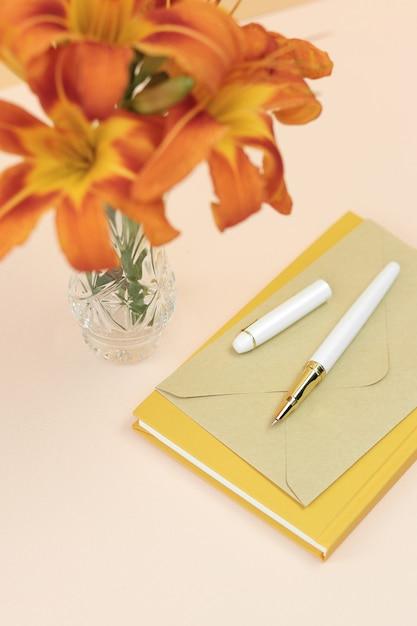 Bouquet de lis orange dans un vase avec cahier jaune et enveloppe Photo Premium