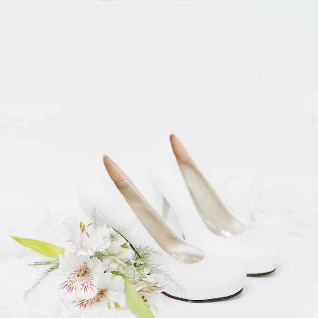 Bouquet De Lis Péruvien Près De La Paire De Mariage De Talons Hauts Isolé Sur Fond Blanc Photo gratuit