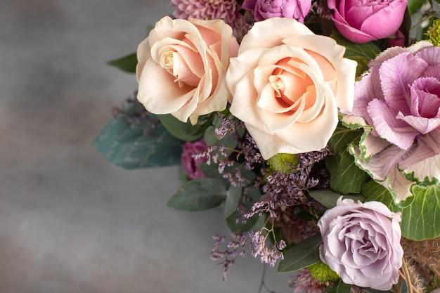 Bouquet Lumineux De Différentes Variétés De Roses Avec Une Rosette De Brassica Sur Fond Gris. Image Horizontale, Espace De Copie Photo Premium