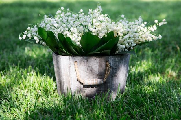 Bouquet de lys de la vallée dans un panier. fond floral avec des endroits pour votre texte Photo Premium