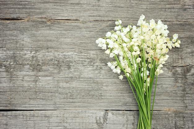 Bouquet de lys de la vallée sur un fond en bois. Photo Premium