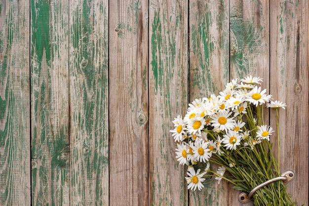 Bouquet de marguerites à la camomille dans la porte poignée clôture vieilles planches en bois Photo Premium