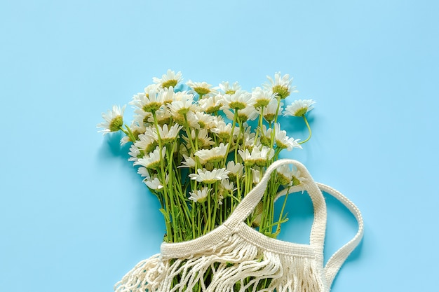 Bouquet de marguerites dans un sac en maille eco réutilisable sur fond bleu Photo Premium