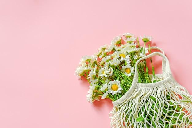 Bouquet de marguerites dans un sac en maille eco réutilisable sur fond rose. Photo Premium