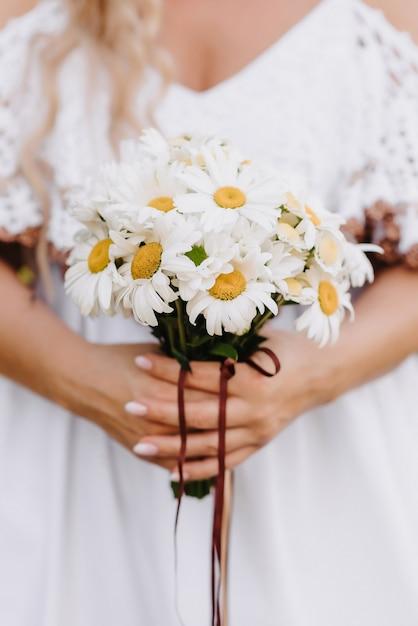 Bouquet De Marguerites Entre Les Mains De La Mariée Sur Le Fond D'une Robe Blanche Photo Premium