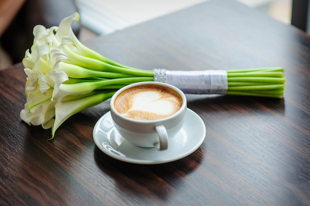 Bouquet De Mariage De Lis Calla Sur Une Table Avec Une Tasse De Café. Photo Premium