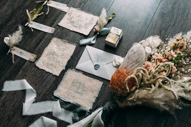 Bouquet De Mariée Arts Graphiques Et Rustiques De Belles Cartes De Calligraphie Avec Des Bobines De Fleurs Et De Mousseline Sur Table En Bois. Belle Invitation De Mariage. Vue De Dessus. Photo Premium