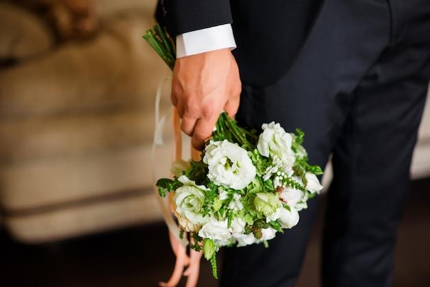 Bouquet De Mariée Entre Les Mains Du Marié. Photo Premium