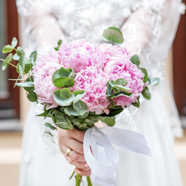 Bouquet de mariée de fleurs de pivoine rose dans les mains de la mariée Photo Premium