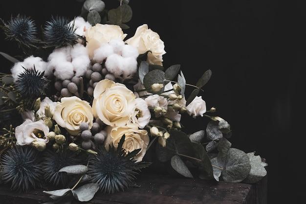 Bouquet De Mariée D'hiver De Roses Blanches, De Coton Et D'eringium Sur Fond Noir. Le Bouquet De La Mariée. Photo Premium