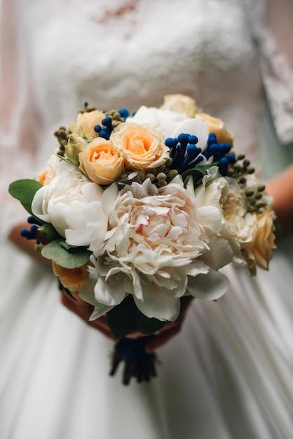 Bouquet De Mariée De Pivoines Blanches Et De Roses Dans Les Mains Photo Premium