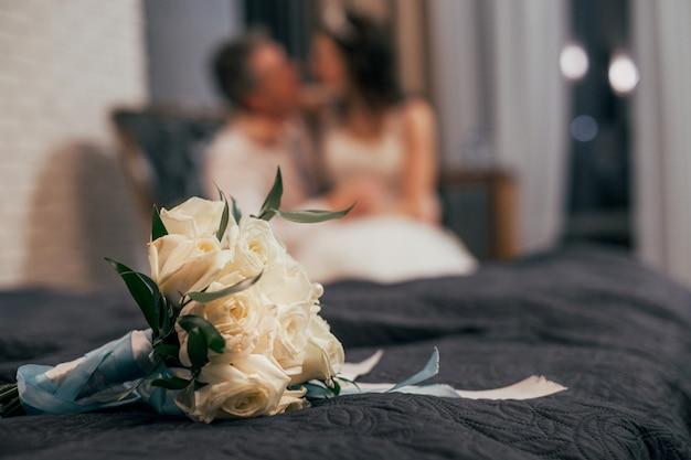Bouquet de mariée de roses blanches sur le lit, couple flou sur le fond Photo Premium