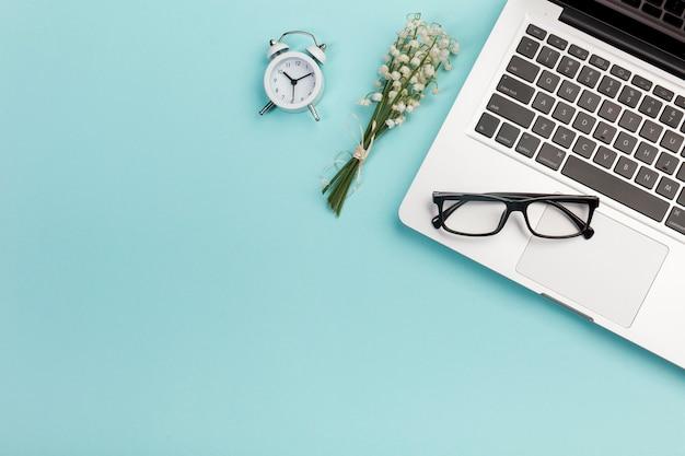 Bouquet de muguet avec réveil, lunettes et ordinateur portable sur le bureau bleu Photo gratuit