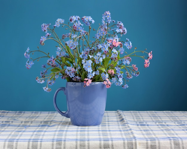 Bouquet de myosotis sur la table sur fond bleu. Photo Premium