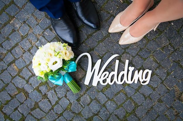 Bouquet et un panneau en bois au mariage est le couple de pieds Photo Premium