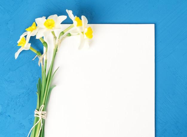 Bouquet de papier blanc vierge de jonquilles fleurs fraîches en fond de béton texturé bleu Photo Premium