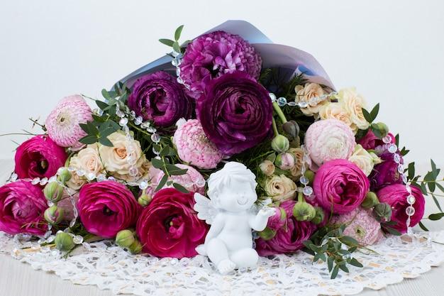 Un bouquet de renoncules, de roses, de perles transparentes et d'un ange blanc Photo Premium