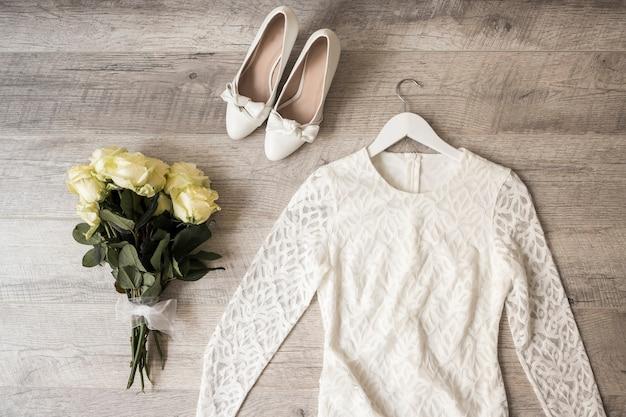 Bouquet de rose; robe de mariée; et chaussures habillées sur fond en bois Photo gratuit