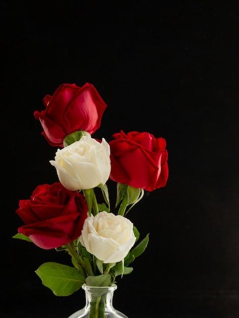 Bouquet rose rouge et blanc dans un vase en verre sur fond noir Photo Premium