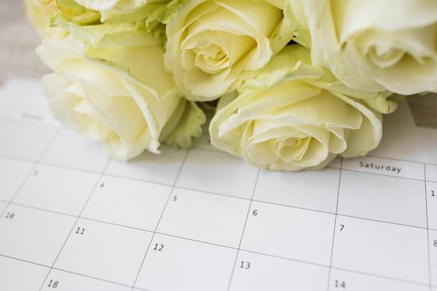Bouquet de roses sur calendrier avec dates Photo gratuit