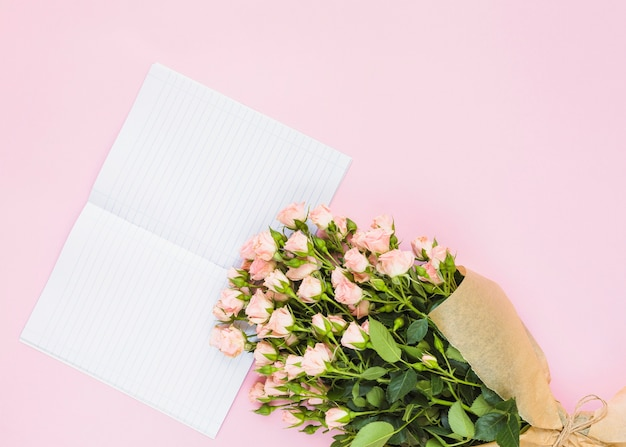 Bouquet de roses et carnet de notes d'une seule ligne sur fond rose Photo gratuit