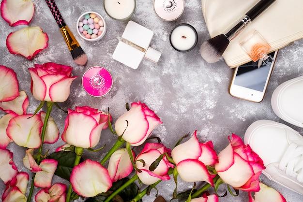 Bouquet De Roses Avec Des Cosmétiques En Parfum, Téléphone Et Baskets Sur Fond Gris Photo Premium
