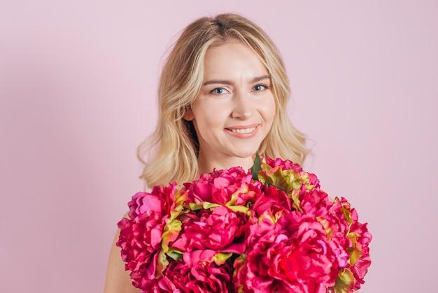 Bouquet De Roses De Fleurs Rouges En Face De La Souriante Jeune Femme Sur Fond Rose Photo gratuit
