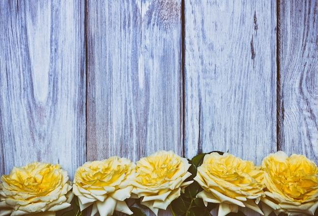 Bouquet de roses jaunes sur un fond en bois blanc Photo Premium