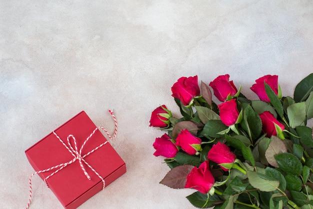 Un bouquet de roses rouges et une boîte cadeau rouge Photo Premium