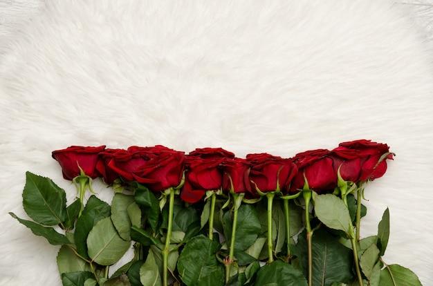 Bouquet de roses rouges sur fond de fourrure blanche Photo Premium