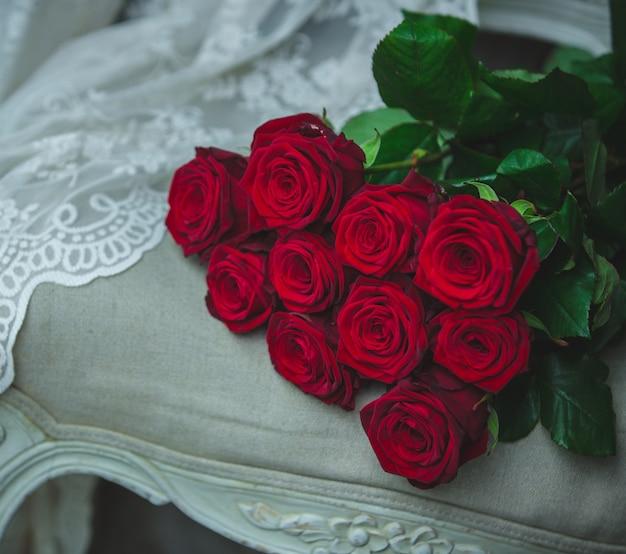 Bouquet de roses rouges se tenant sur une chaise de couleur beige avec des rideaux. Photo gratuit