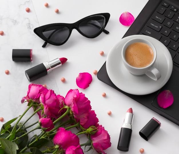 Bouquet de roses, tasse de café, ordinateur portable, lunettes de soleil et rouge à lèvres sur un tableau blanc. Photo Premium