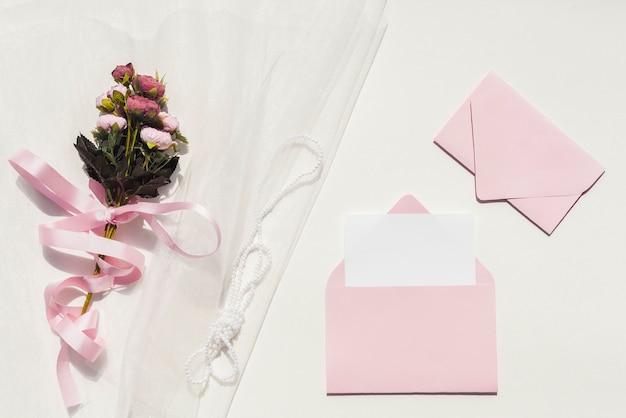 Bouquet De Roses Sur Le Voile à Côté Des Invitations De Mariage Photo gratuit